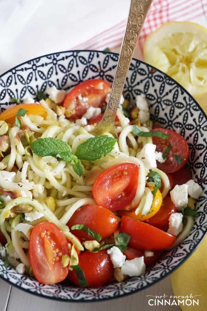close-up of a bowl of zucchini noodle salad with tomatoes, feta, mint and pistachios