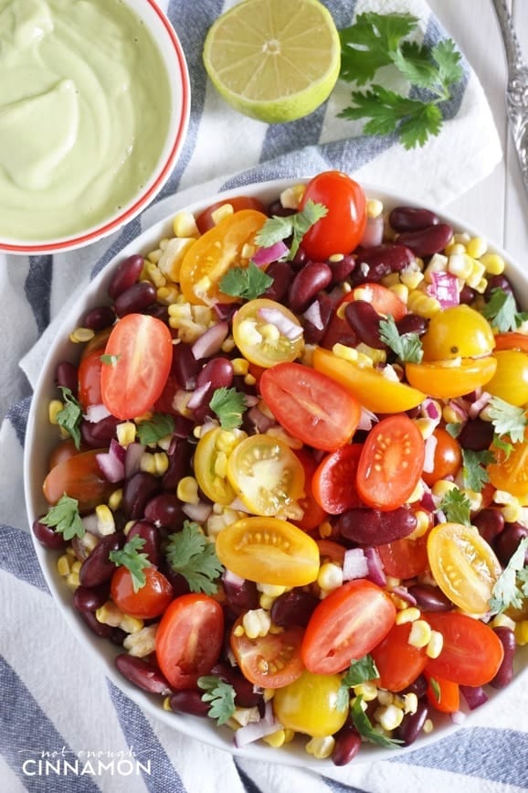 close-up of a bowl of corn, black bean & tomato salad with vegan avocado lime dressing on the side
