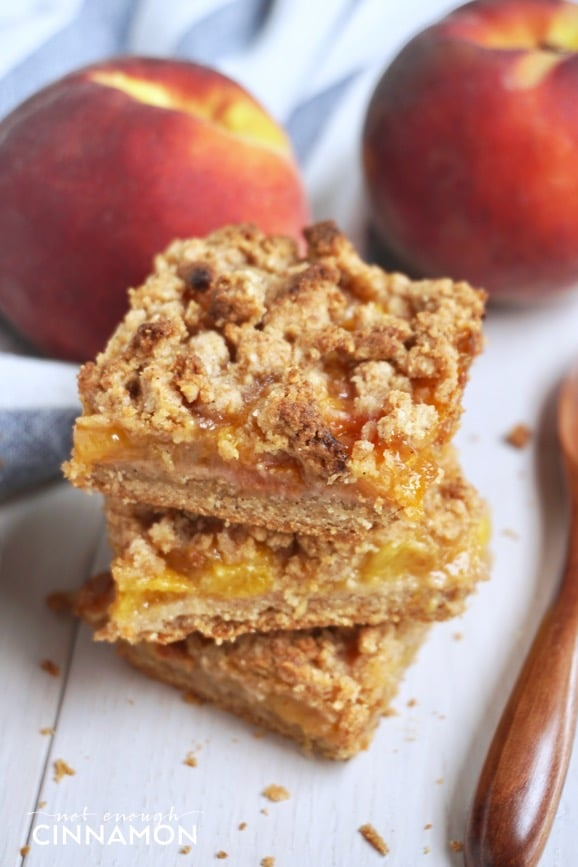 a stack of three healthy peach crisp bars with peaches in the background