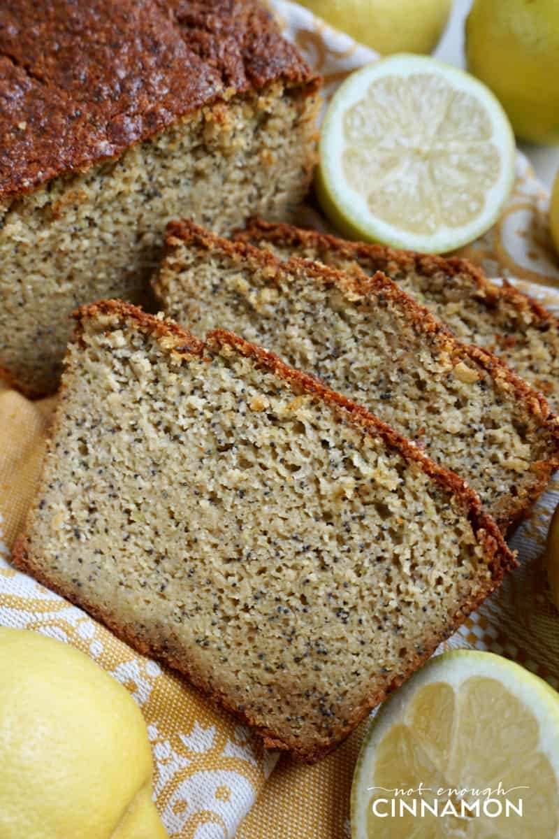 three slices of moist paleo zucchini bread with lemon and poppy seeds with halved lemons on the side