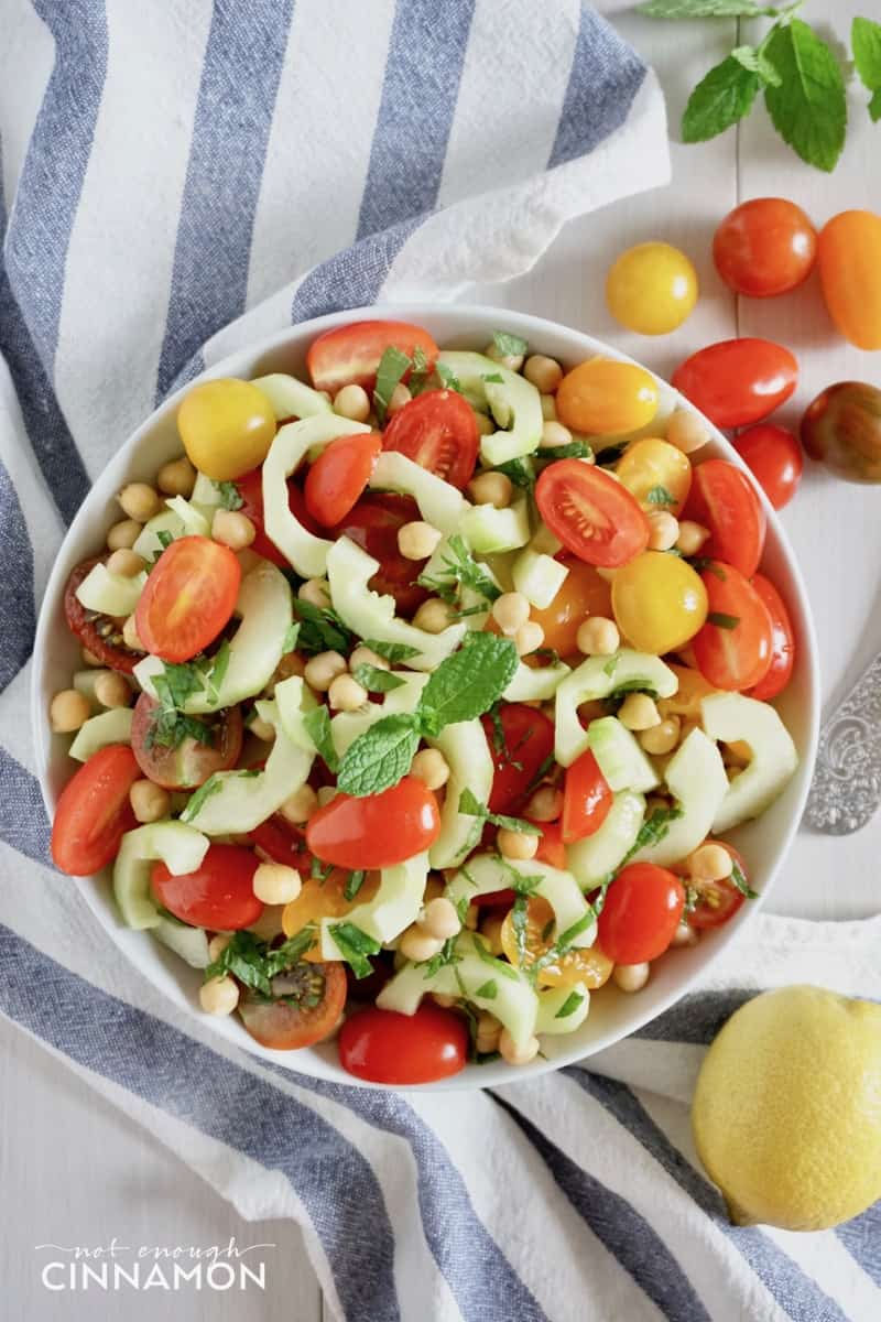overhead shot of a simple chickpea salad with tomatoes, cucumber and mint in a bowl