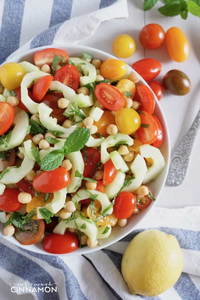 overhead shot of a bowl of simple chickpea salad with tomatoes, cucumber and mint