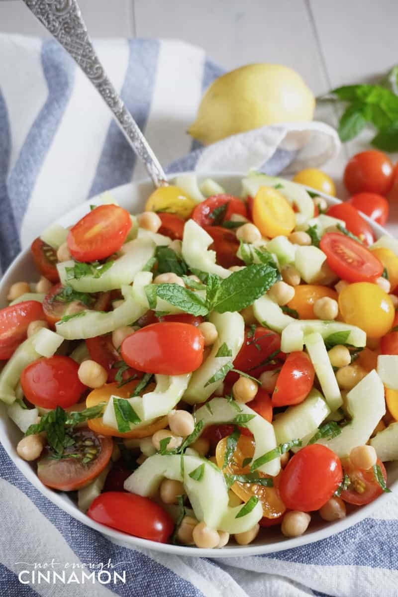 close-up of vegan chickpea salad with cucumber, mint and tomatoes in a white bowl