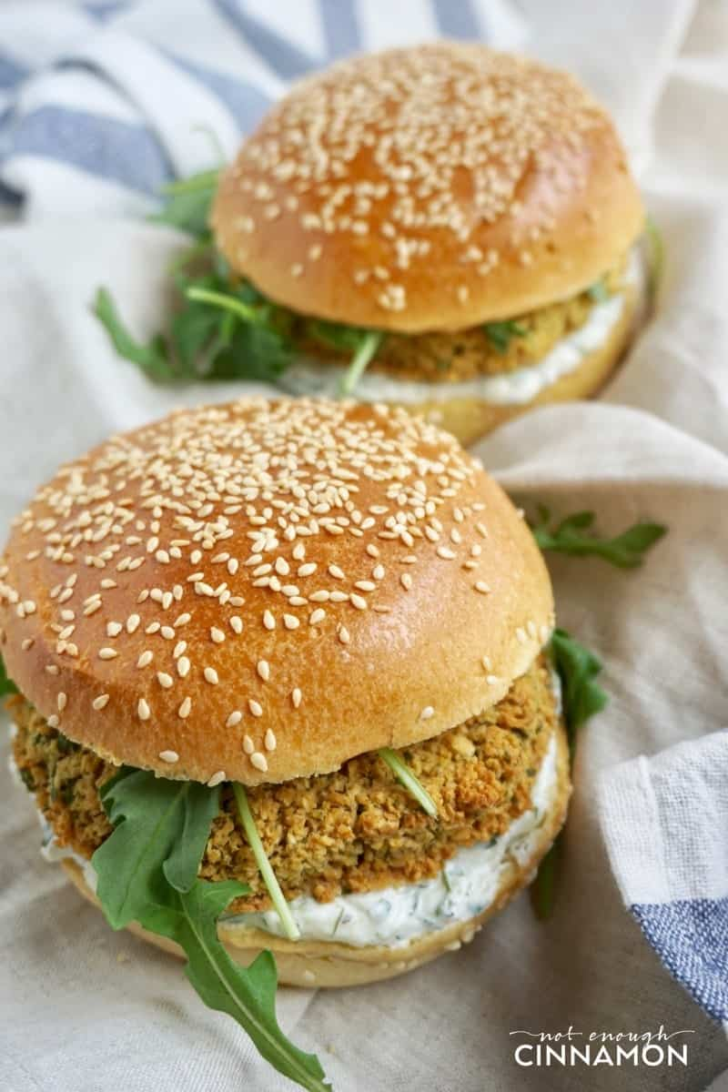 two vegetarian falafel burgers with falafel patties, tzatziki, and fresh arugula on a striped kitchen towel