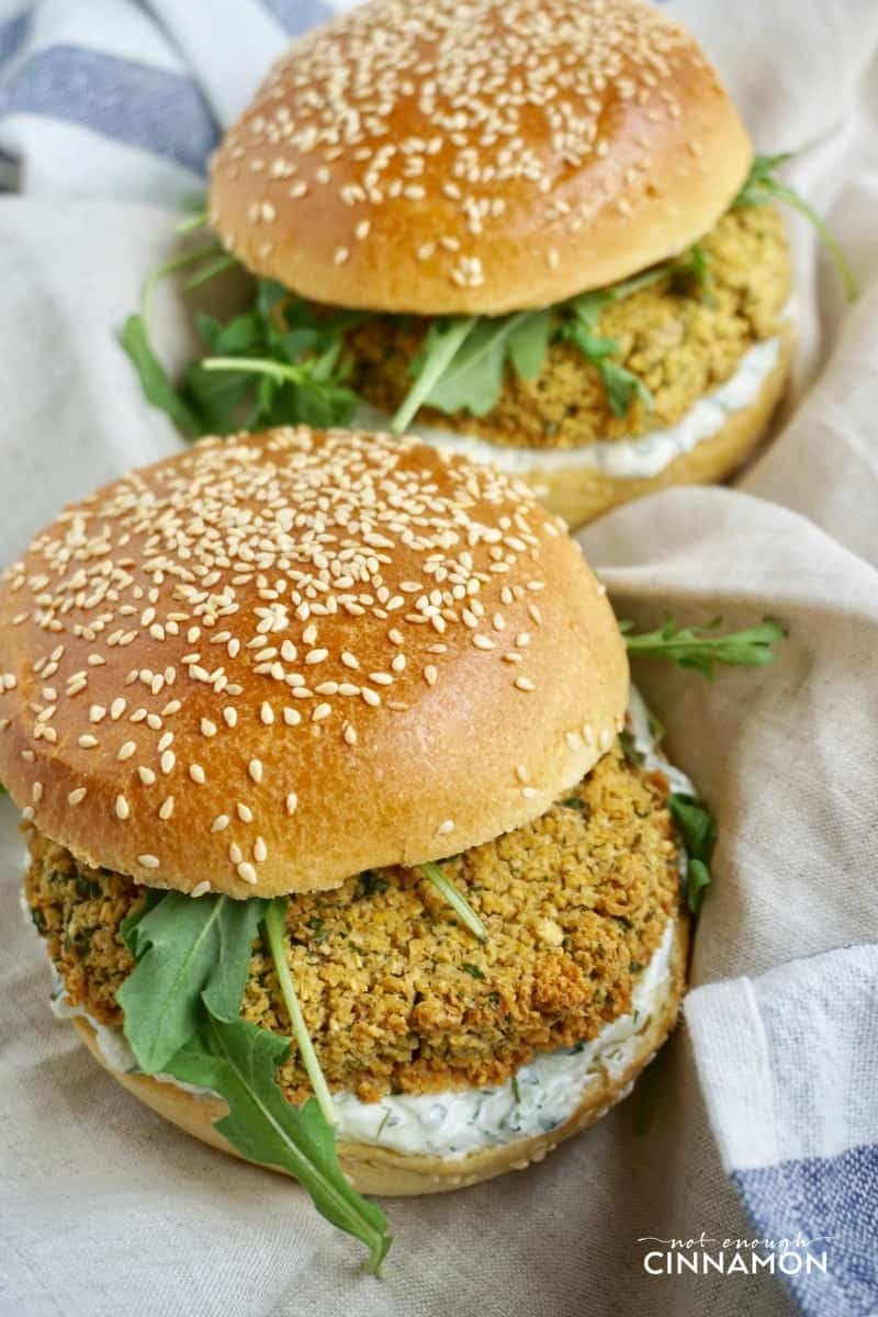 side view of two falafel burgers with falafel patties, fresh arugula and tzatziki sauce