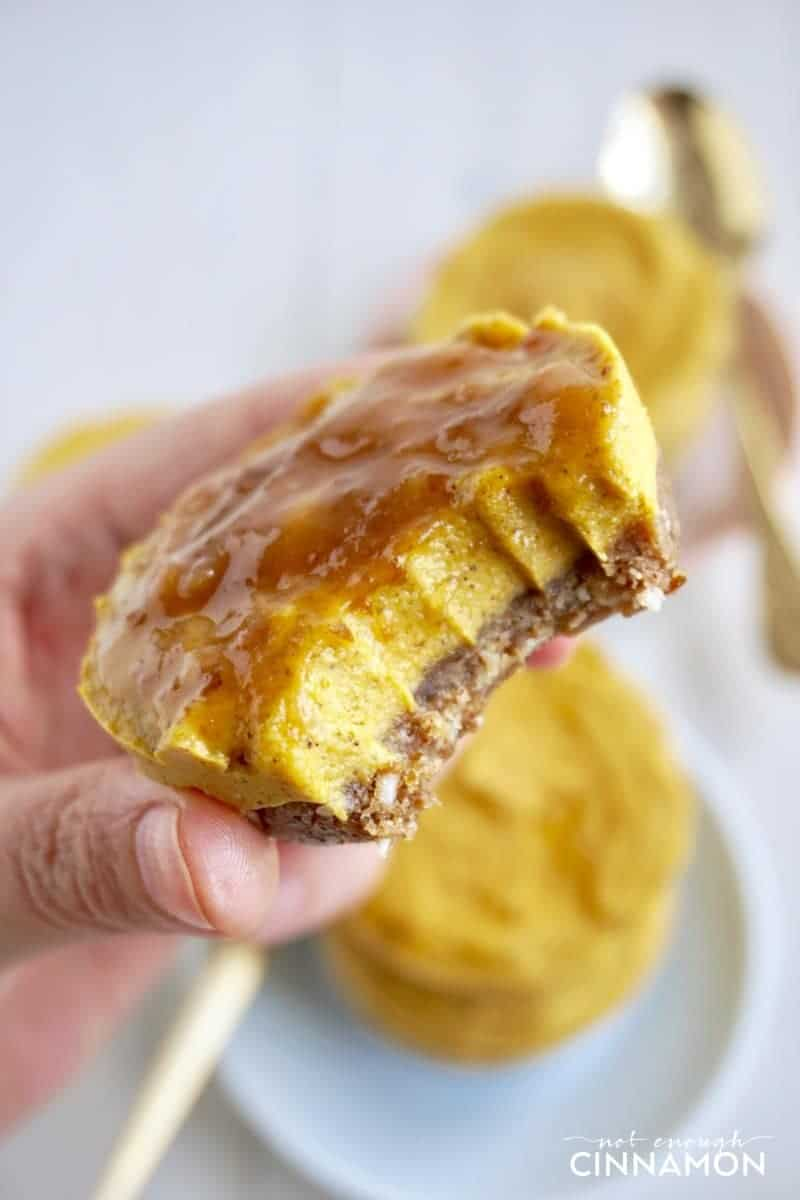 a hand holding a bite-sized vegan pumpkin cheesecake with caramel topping