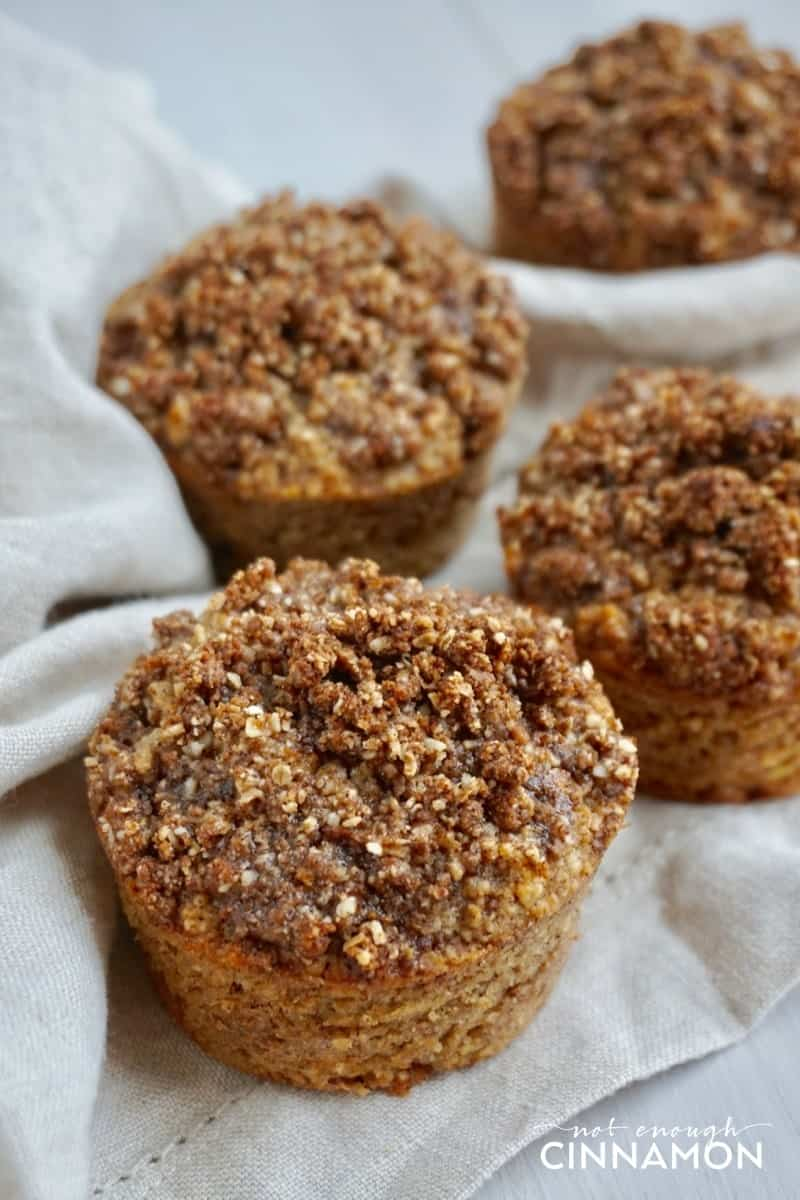 Gluten Free Apple Snickerdoodle Muffins on a white tablecloth