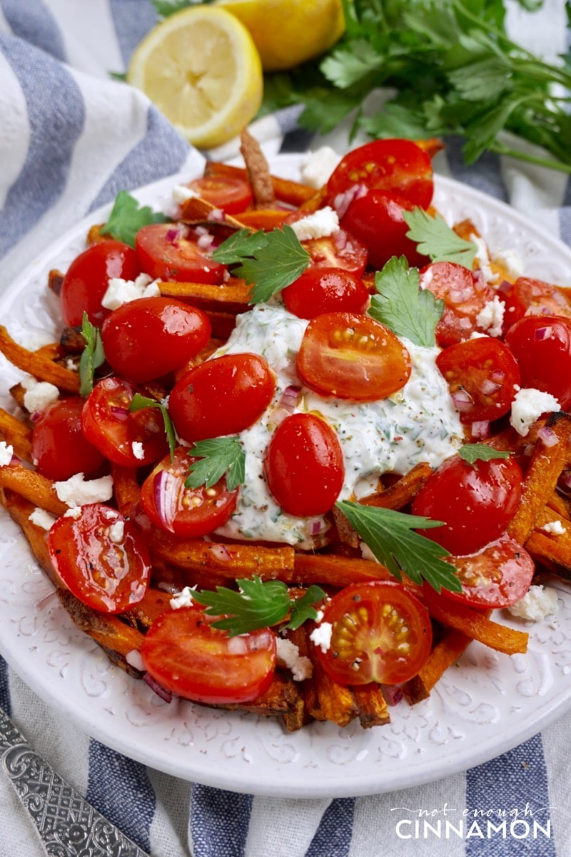 side view of a plate of Loaded Sweet Potato Fries topped with tzatziki, feta and tomato salad.
