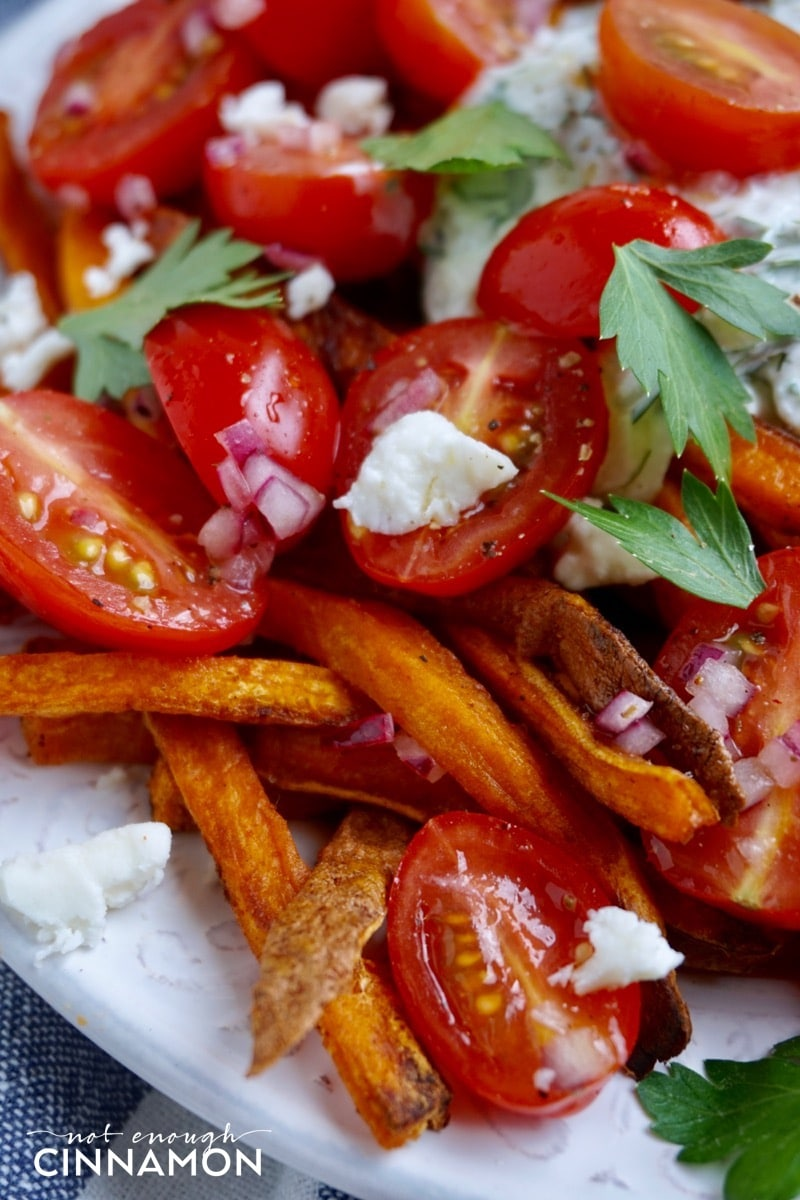 close-up of vegetarian Loaded Sweet Potato Fries with tzatziki, feta and tomato salad.