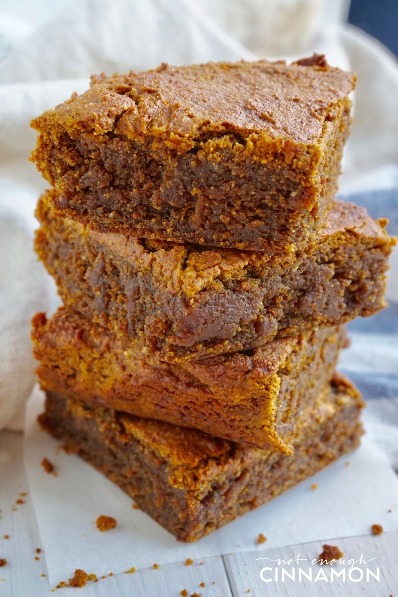 A stack of four Paleo Pumpkin Blondies on a piece of parchment paper
