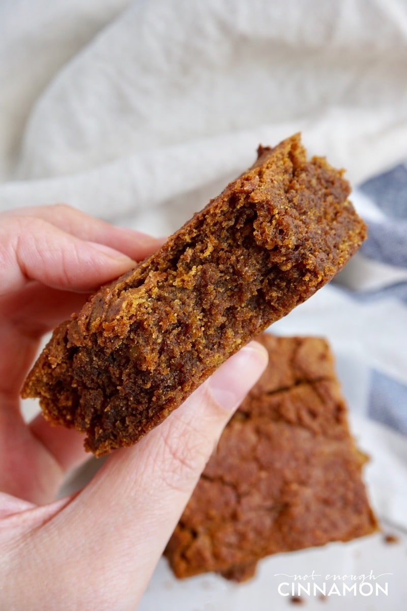 a hand holding a Vegan Paleo Pumpkin Blondie with one bite missing