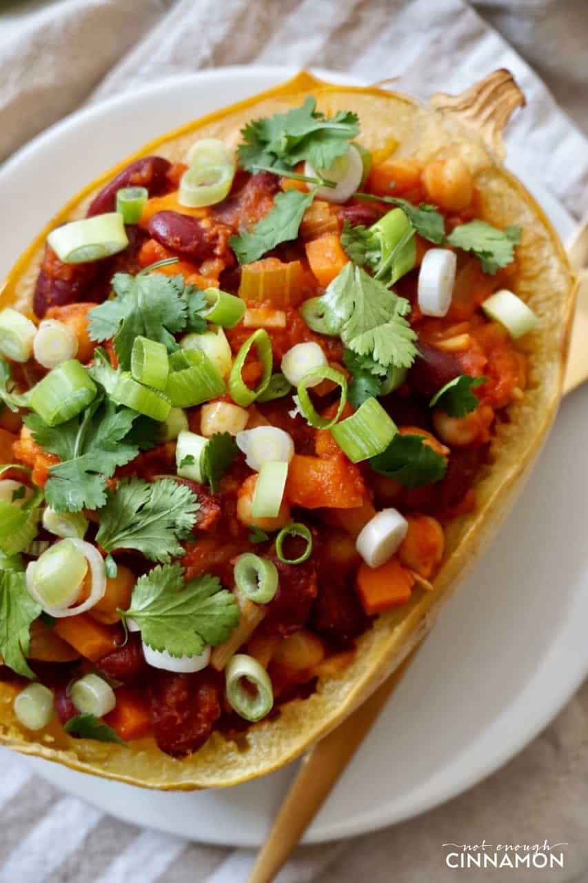overhead shot a spaghetti squash boats filled with vegan chili and sprinkled with cilantro and scallions