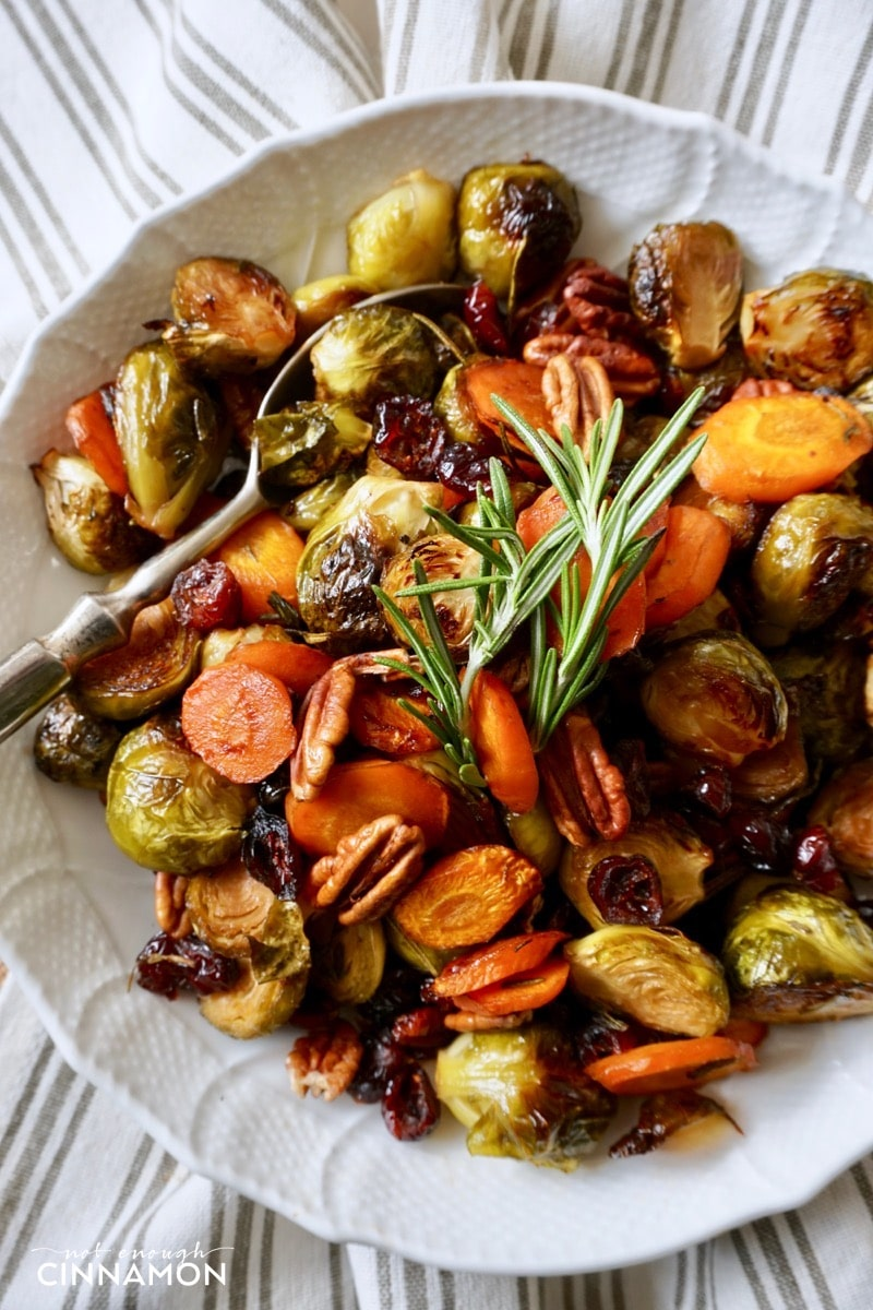 overhead shot of a plate of maple roasted vegetables with balsamic vinegar, rosemary and pecans