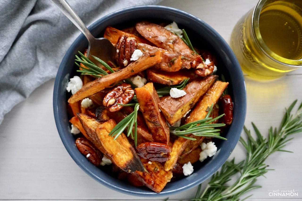 a small bowl with Sweet potato wedges, crumbled goat cheese, rosemary and candied pecans
