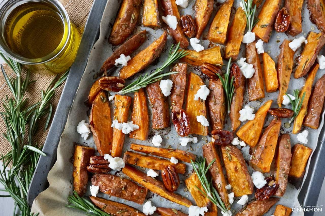 overhead shot of Sweet potato wedges on a baking sheet drizzled with olive oil, goat cheese and candied pecans