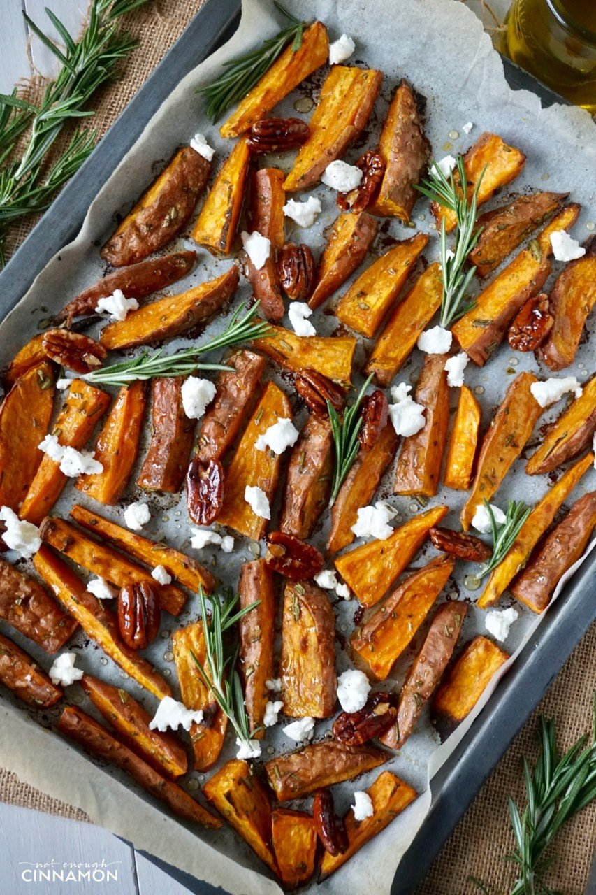 overhead shot of Sweet potato wedges on a baking sheet drizzled with olive oil and sprinkled with goat cheese and candied pecans