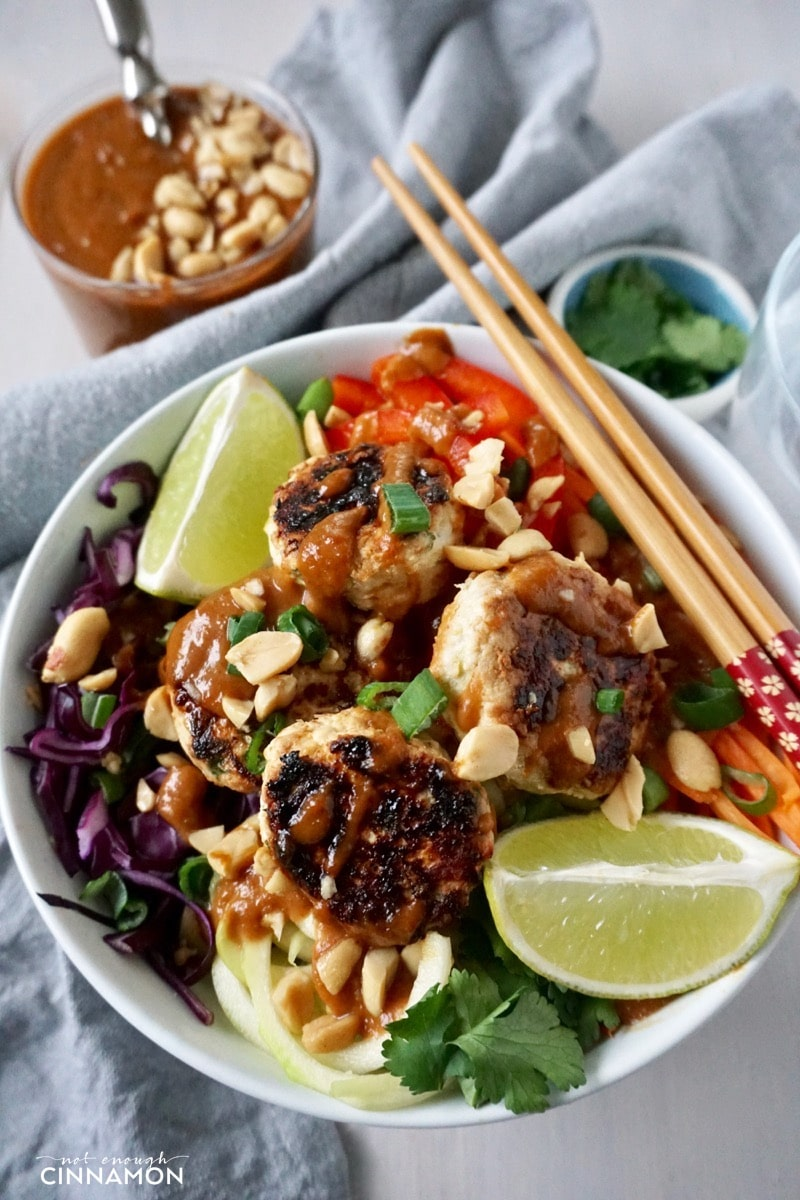 close-up of a Thai veggie bowl with veggie noodles and mini Thai chicken patties drizzled with peanut sauce