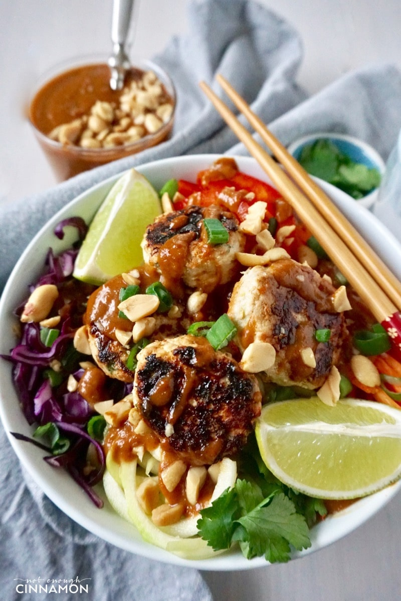 A Thai veggie bowl with spiralized veggies and mini Thai chicken patties drizzled with peanut sauce