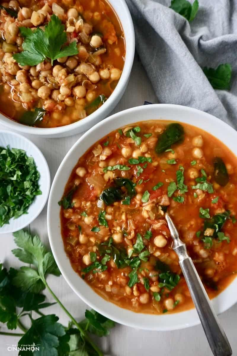 overhead shot of two bowls of Moroccan chickpea soup sprinkled with parsley