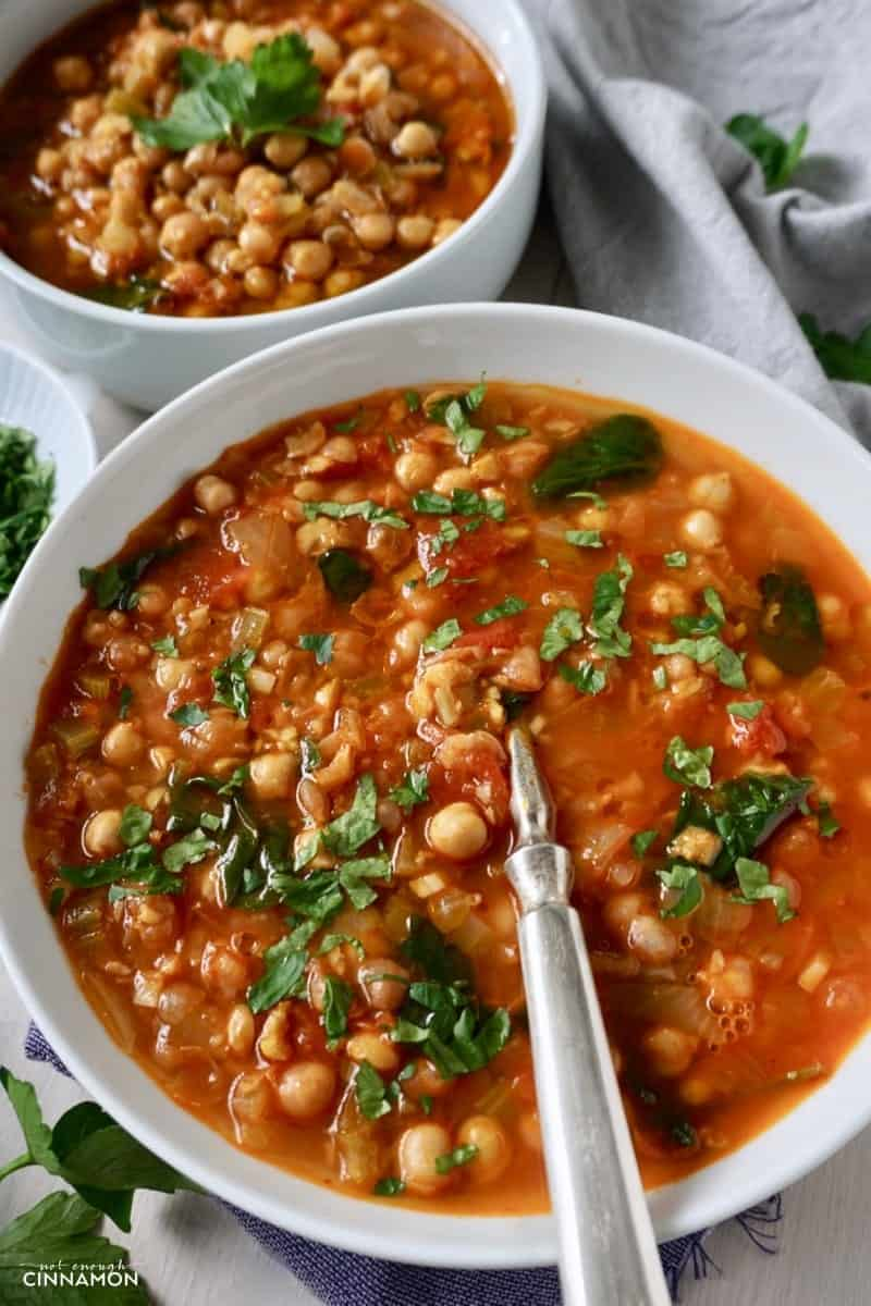 Close-up of a white bowl of Moroccan chickpea soup spiced with cumin, paprika and cinnamon