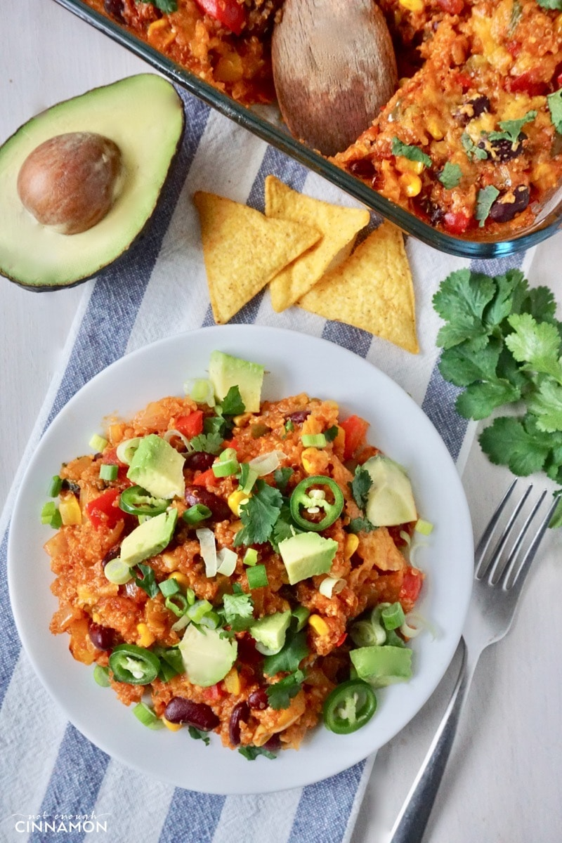 overhead shot of a plate with Mexican quinoa casserole with a casserole dish, nacho chips and an avocado in the background