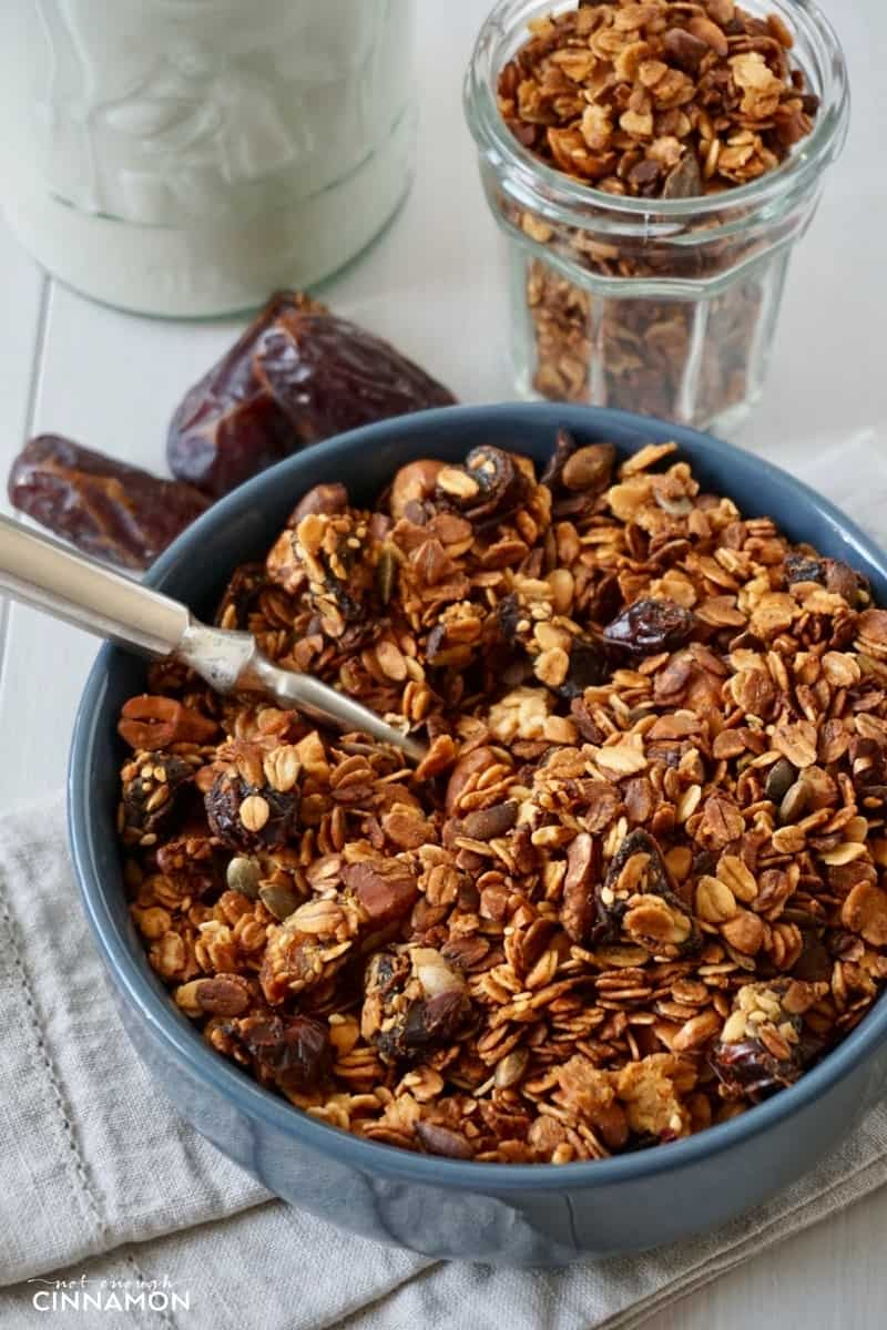 a blue bowl filled with homemade baked honey granola with dates and cashews