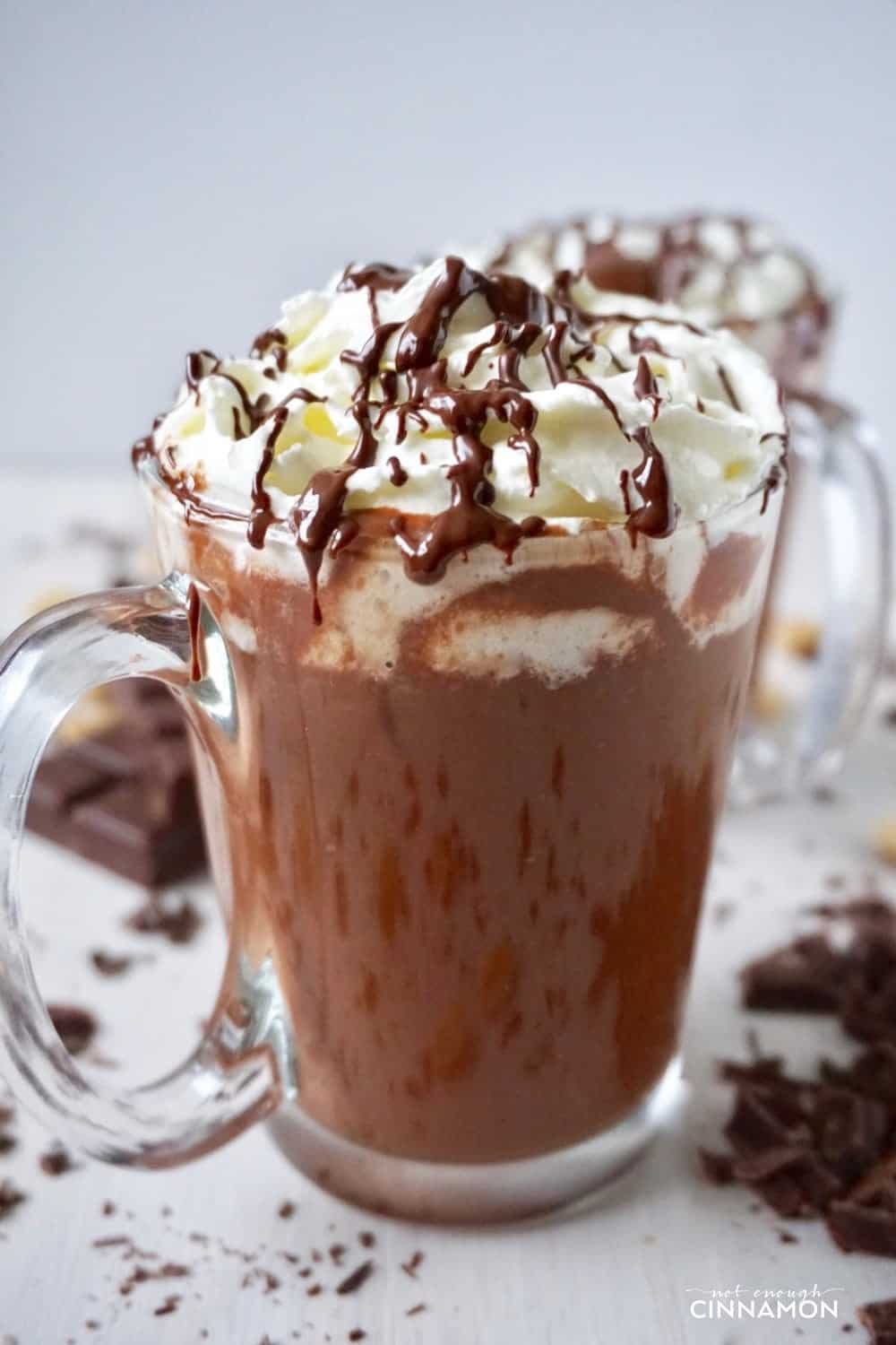 side view of a mug of Healthier peanut hot chocolate topped with whipped cream and chocolate sauce