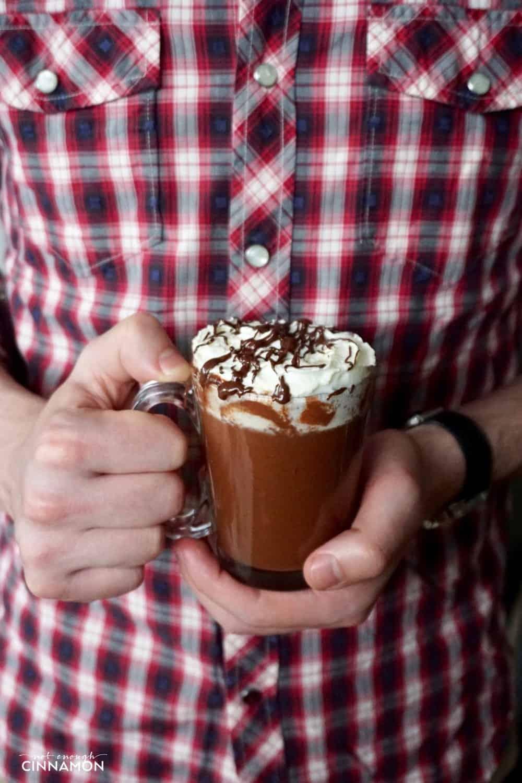 a man in a lumberjack shirt holding a mug of peanut butter hot chocolate