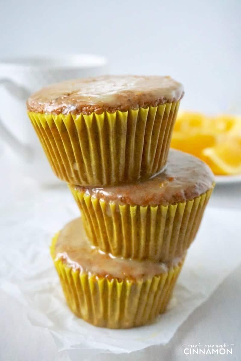 three stacked gluten-free orange poppy seed muffins with vanilla glaze