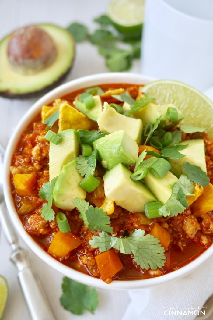 close-up of a bowl if quinoa turkey sweet potato chili topped with avocado cubes and cilantro