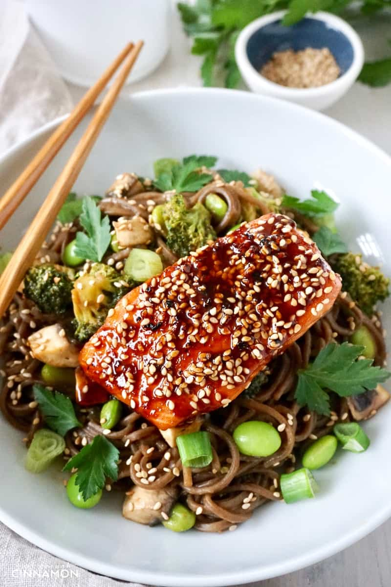 close-up of a maple-glazed salmon fillet on soba noodles, broccoli and edamame beans
