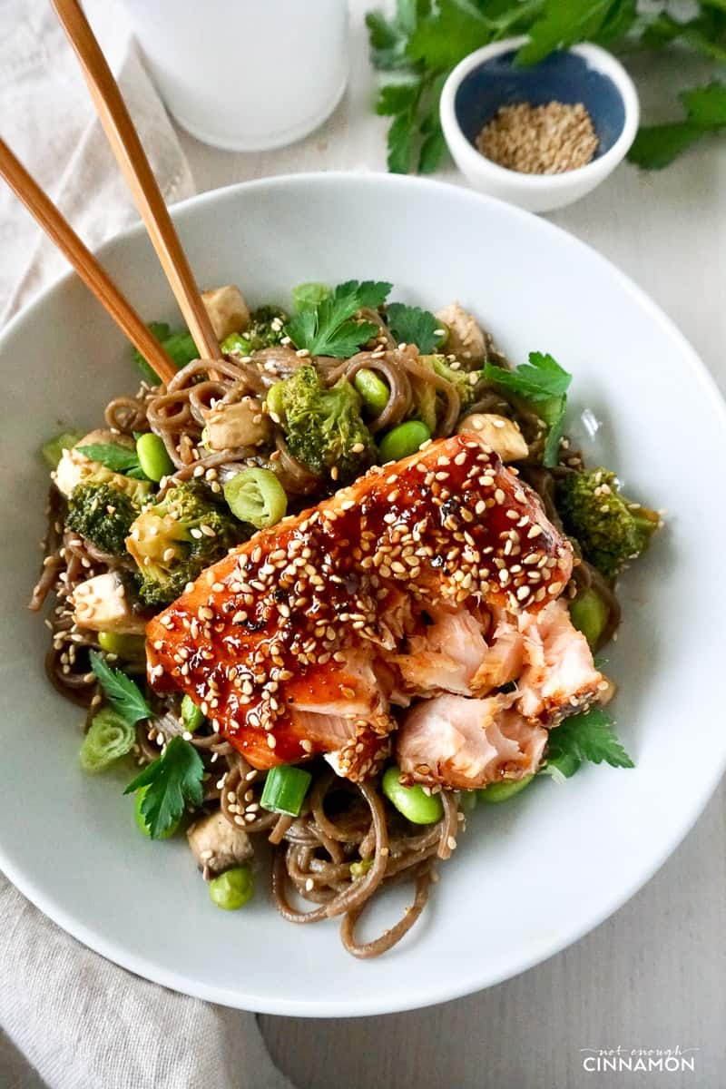 overhead shot of a maple-glazed salmon fillet sprinkled with sesame seeds on a bed of soba noodles and veggies