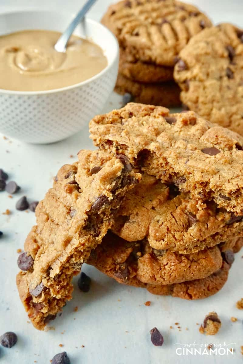 Healthier Peanut Butter and Chocolate Cookies with a dish of smooth peanut butter in the background