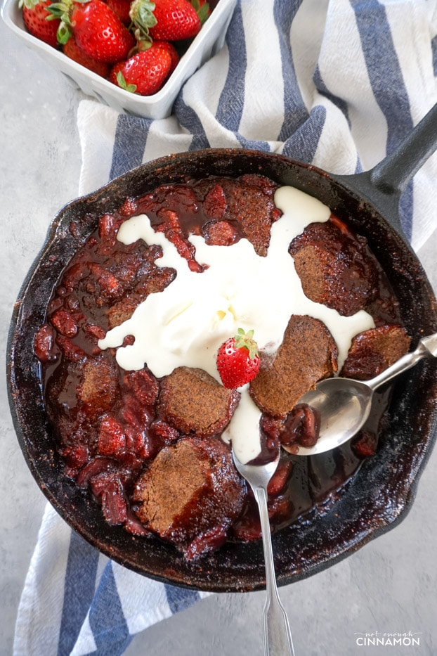 Strawberry Cobbler in a cast iron skillet, with two spoons and melting ice cream scoops on top.