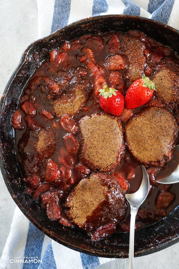 Strawberry cobbler in a cast iron skillet over a white and blue stripped dish towel, with two spoons and two fresh strawberries on top.