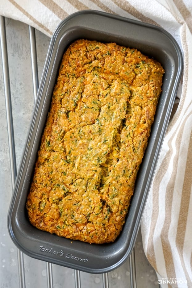 Overhead shot of a cheddar chive zucchini bread in a metal pan, right out of the oven on a metallic grill.