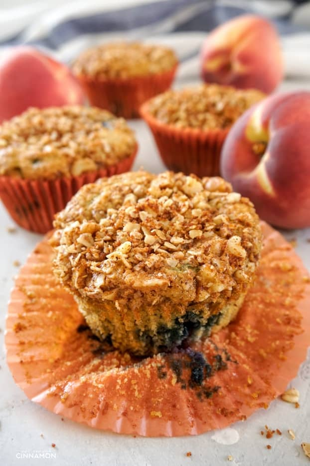 A peach and blueberry muffin with an orange liner opened up, and other muffins and peaches in the background.