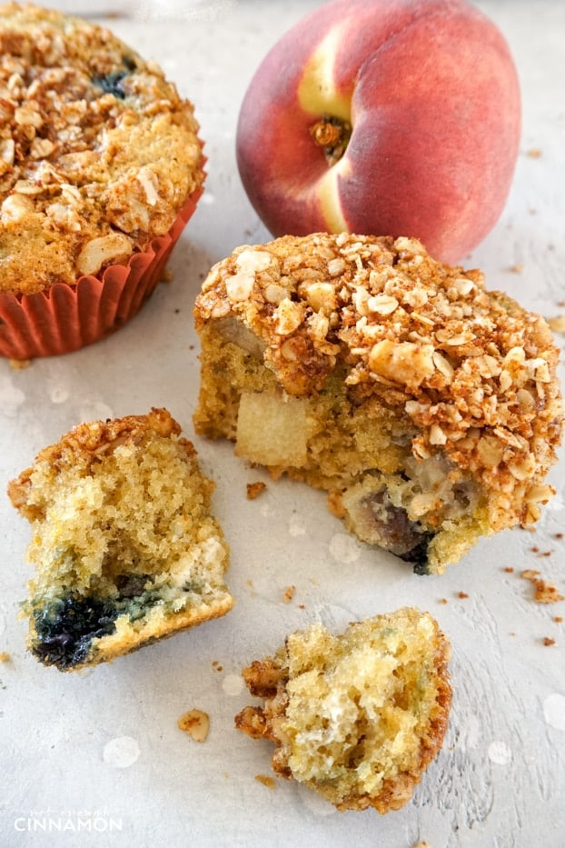 A peach and blueberry muffin torn into a few pieces to show the fruit pieces on the inside.
