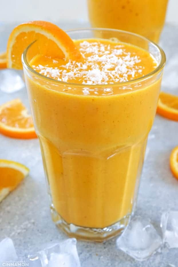 A tall glass of sunshine smoothie with shaved coconut and an orange half wheel