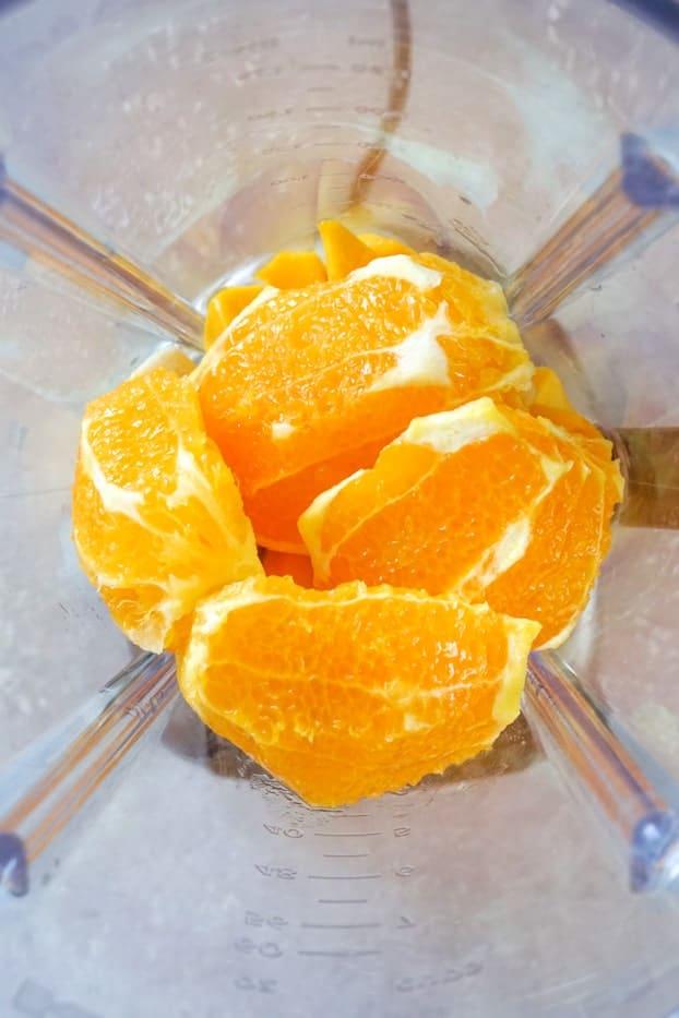 Orange quarters in a blender
