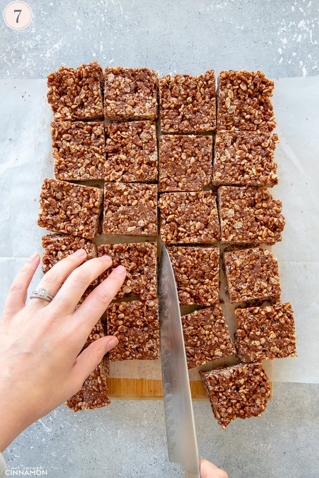 Chocolate rice krispies treats cut in squares with a large knife