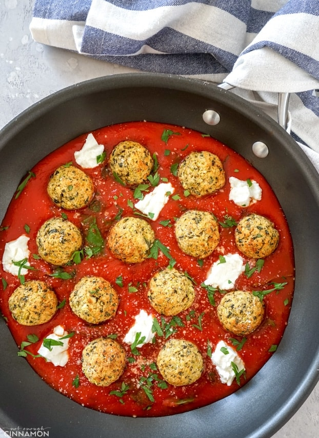 Zucchini meatballs with marinara sauce in a skillet, with a stripped kitchen towel