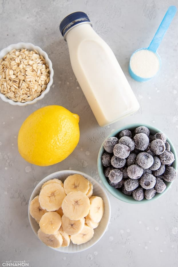 Ingredients for lemon blueberry smoothie: frozen banana and blueberries, oats, a lemon, some milk and protein powder