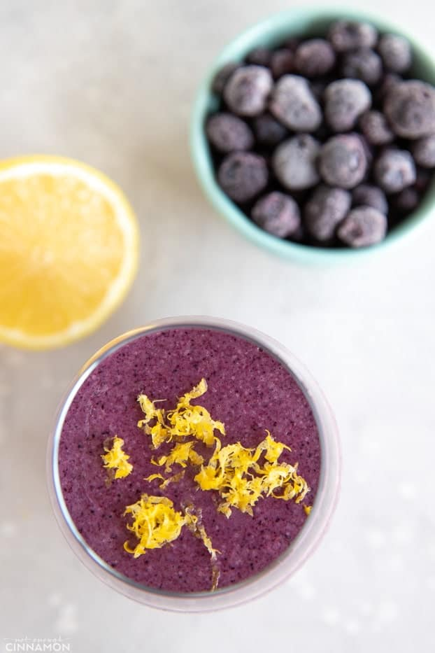 Lemon blueberry smoothie topped with lemon zest, with frozen blueberries and half a lemon on the side