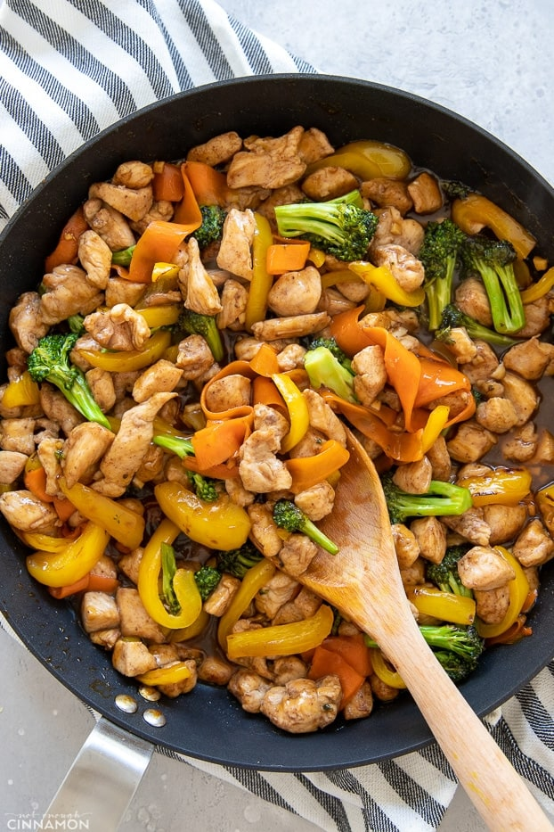 overhead shot of a skillet with Chinese 5-Spice Chicken being stirred with a wooden spoon