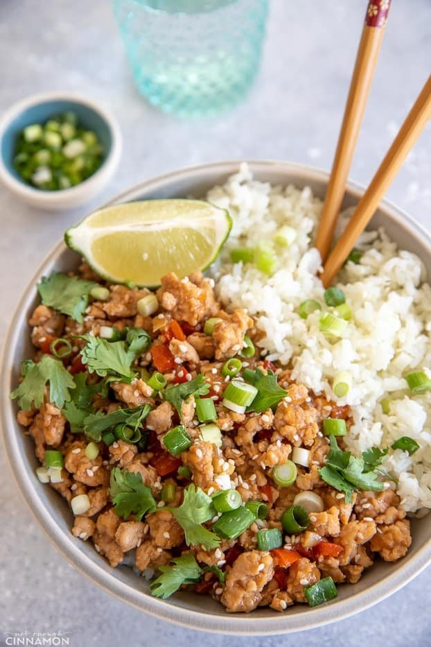 overhead shot of a healthy gluten-free Ground Turkey Rice Bowl served with chopped scallions and a lime wedge