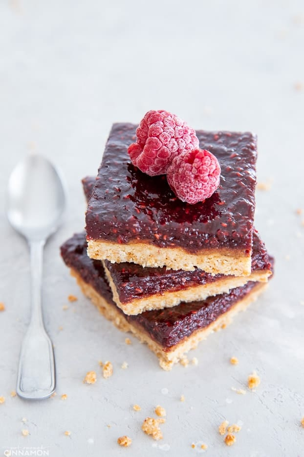 stacked healthy paleo raspberry almond butter bars with a spoon on the side