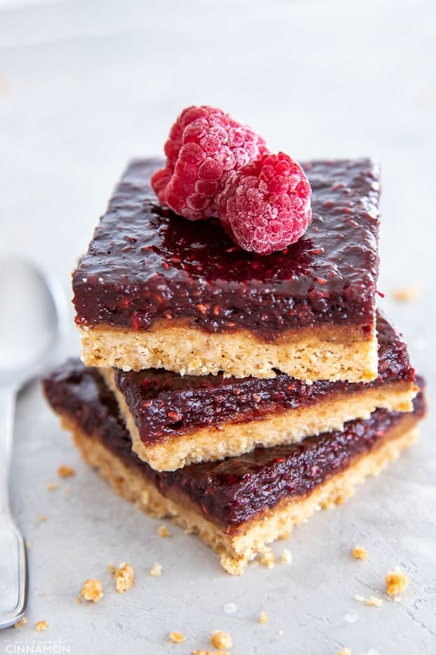 three stacked healthy raspberry almond butter bars with some crumbs on the side