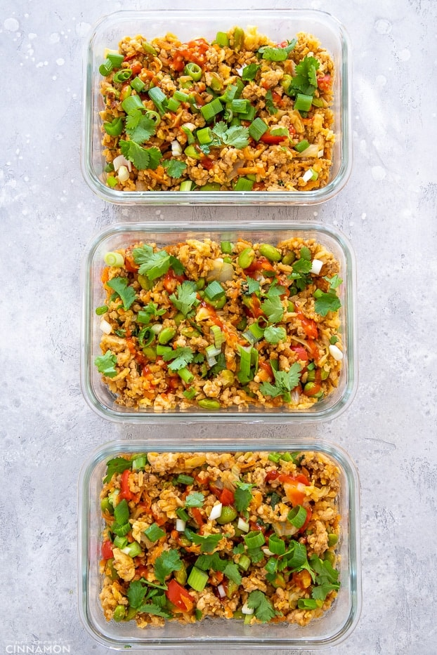 overhead shot of three glass containers with Asian Ground Turkey Fried Rice sprinkled with cilantro and sriracha sauce