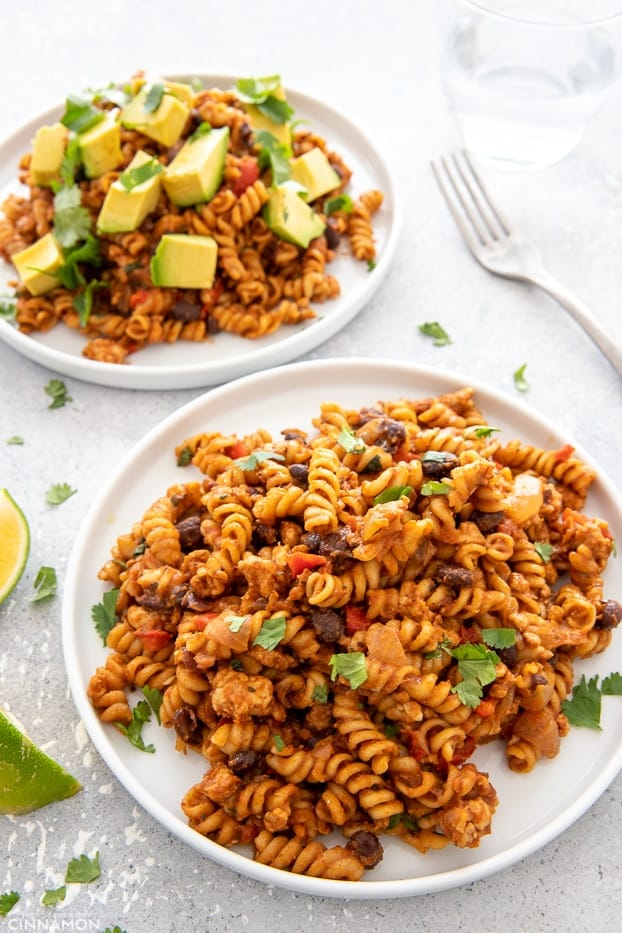 close-up of two servings of one-pot taco pasta loaded with Mexican topping like cilantro and avocado